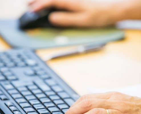 Eine Nahaufnahme von Händen die einen Computer bedienen