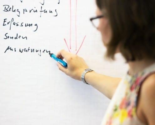 Eine Frau schreibt etwas an ein Flipchart