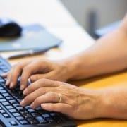 Eine Nahaufnahme von Händen die auf einer Tastatur tippen